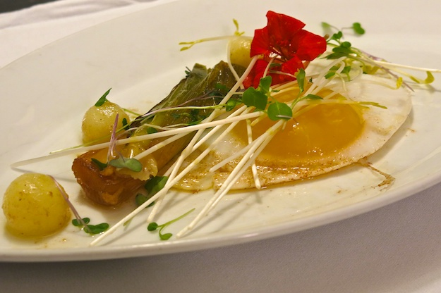 fried duck egg , confit potatoes, thyme butter leeks and fresh herbs (nasturtium)