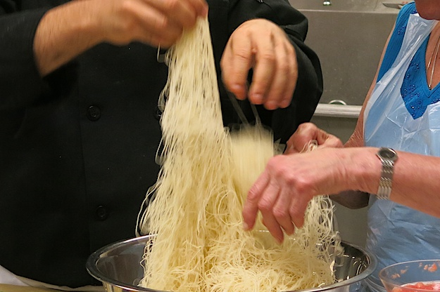 Many hands separating kataif dough for Knafeh